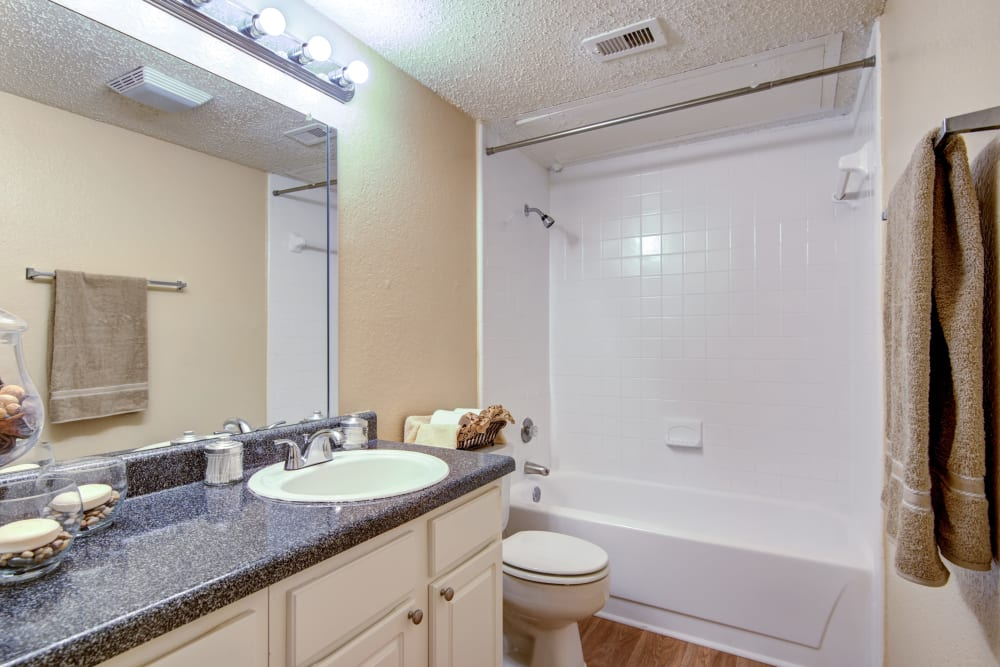 Tiled shower and granite countertop in a model home's bathroom at Grayson Ridge in North Richland Hills, Texas
