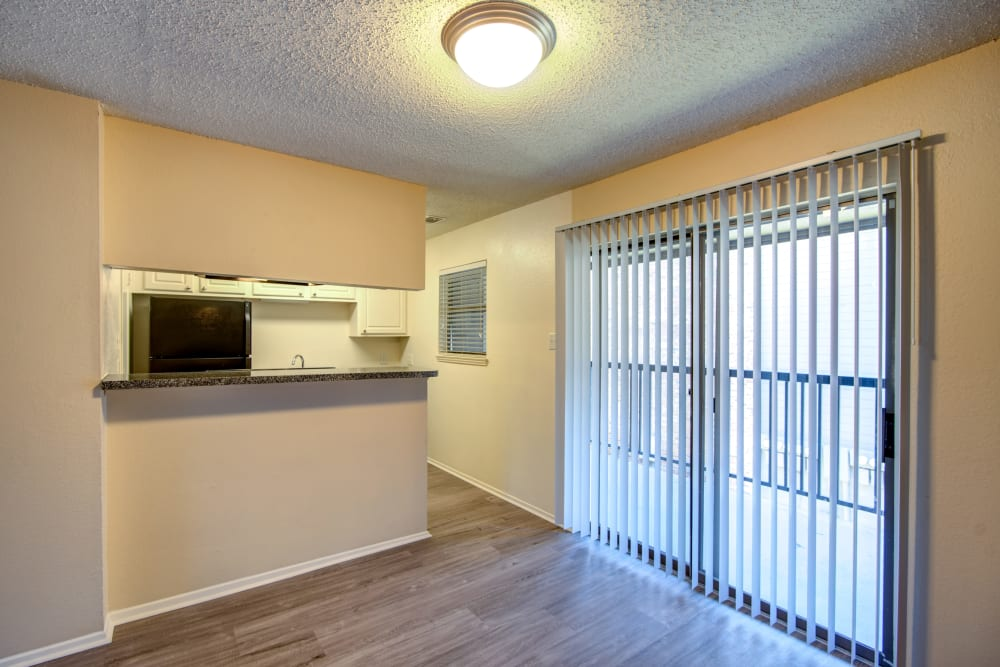 Hardwood floors and a sliding door to the private balcony outside an apartment home at Grayson Ridge in North Richland Hills, Texas