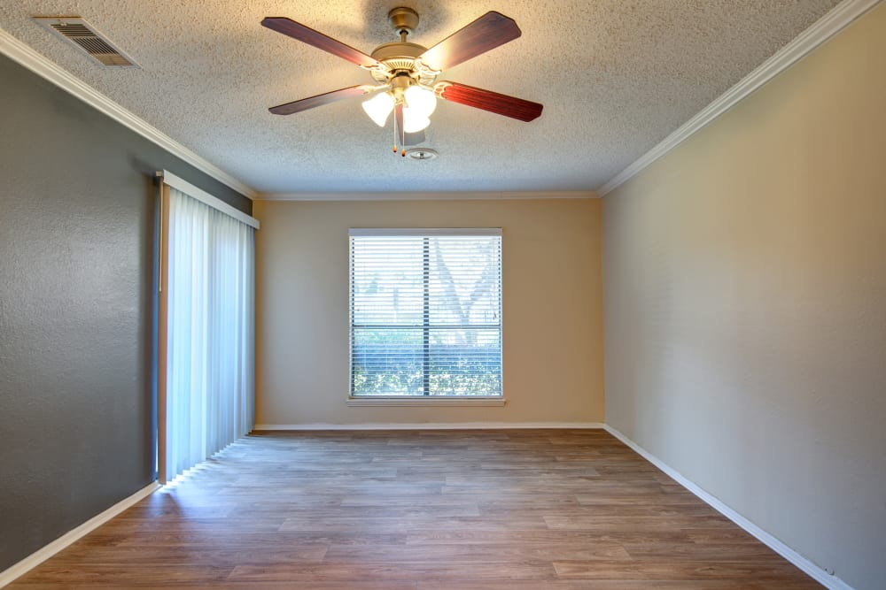 Accent wall, a ceiling fan, and hardwood floors in an apartment home at Grayson Ridge in North Richland Hills, Texas