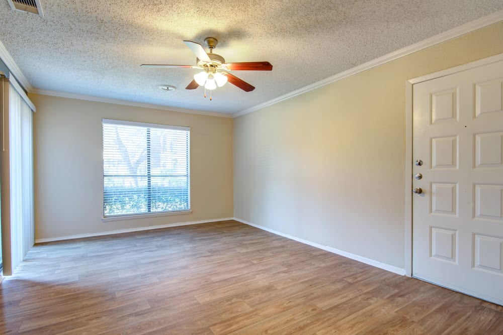 Ceiling fan and large windows letting plenty of natural light into the living space of an apartment home at Grayson Ridge in North Richland Hills, Texas