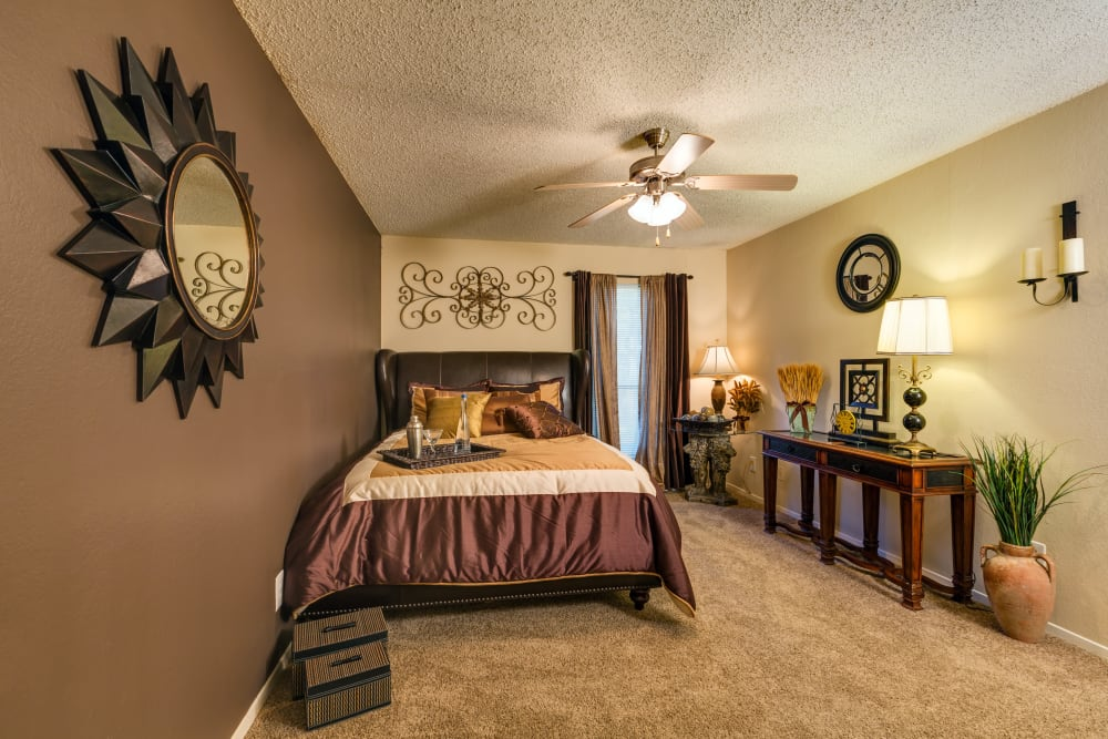 Accent wall, a ceiling fan, and modern furnishings in a model home's master bedroom at Grayson Ridge in North Richland Hills, Texas