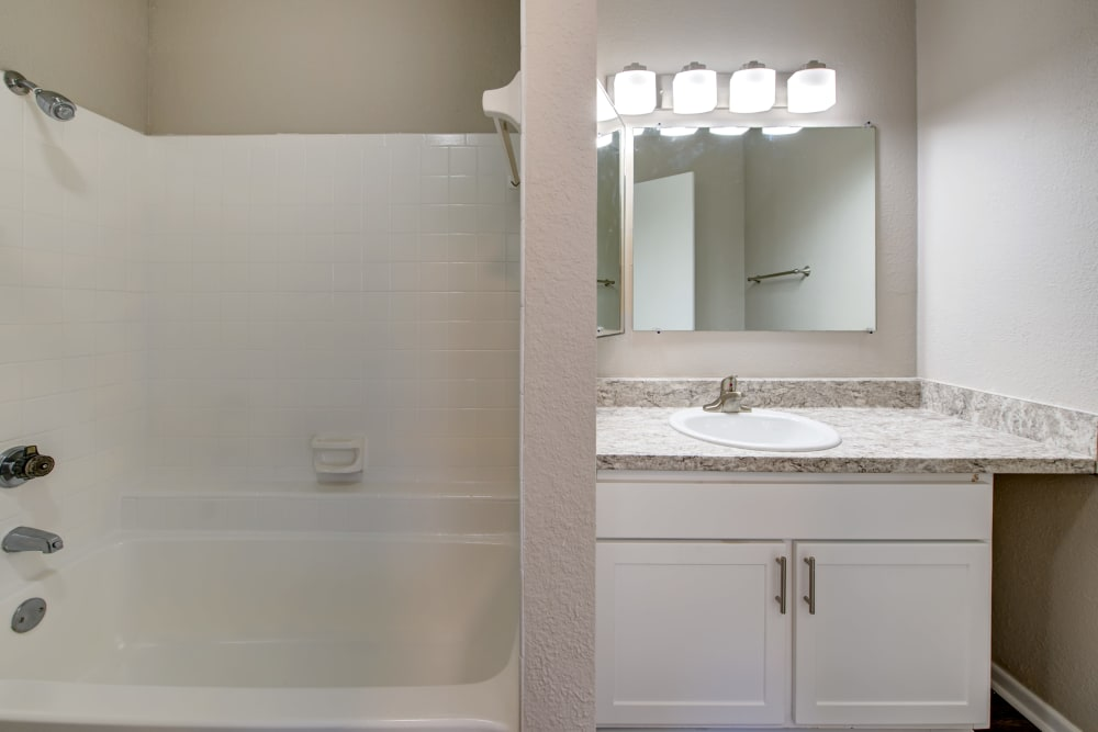 Bathroom with white cabinets and granite counter tops at The Belmont in Grand Prairie, Texas