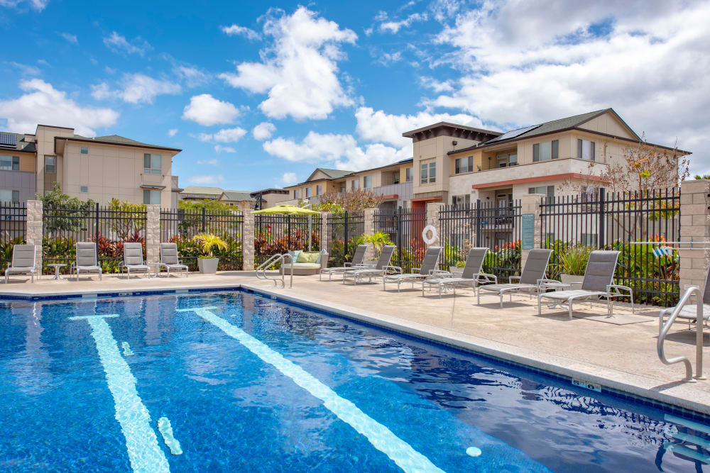 Beautiful swimming pool area with plenty of seating nearby at Kapolei Lofts in Kapolei, Hawaii