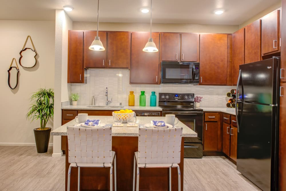 Open-concept floor plan with hardwood floors and custom lighting in model apartment home at Kapolei Lofts in Kapolei, Hawaii