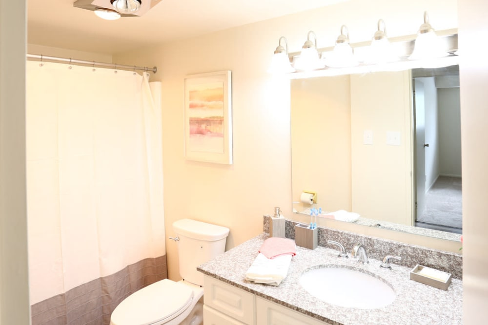 Bathroom with a large vanity mirror at Orchard Hills Apartments in Whitehall, Pennsylvania
