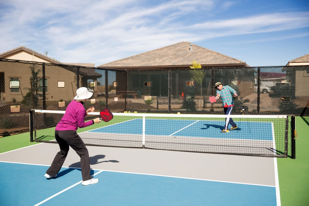 Two residents playing tennis at Touchmark Health & Fitness Club in Meridian, Idaho