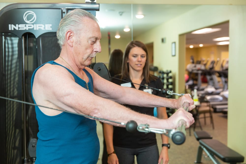 A caretaker assisting a resident with a fitness machine at Touchmark Health & Fitness Club in Meridian, Idaho