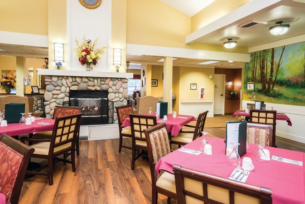 Dining tables in front of a fireplace at Lakeland Senior Living in Eagle Point, Oregon
