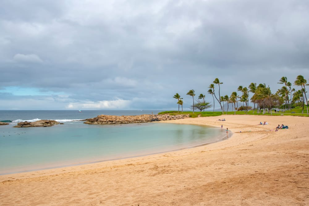 Sandy beach, blue sky, and the ocean lapping at the shore near Kapolei Lofts in Kapolei, Hawaii