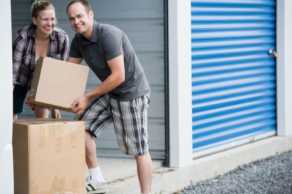 Man helping woman move into storage unit at Towne Storage in Mesa, Arizona