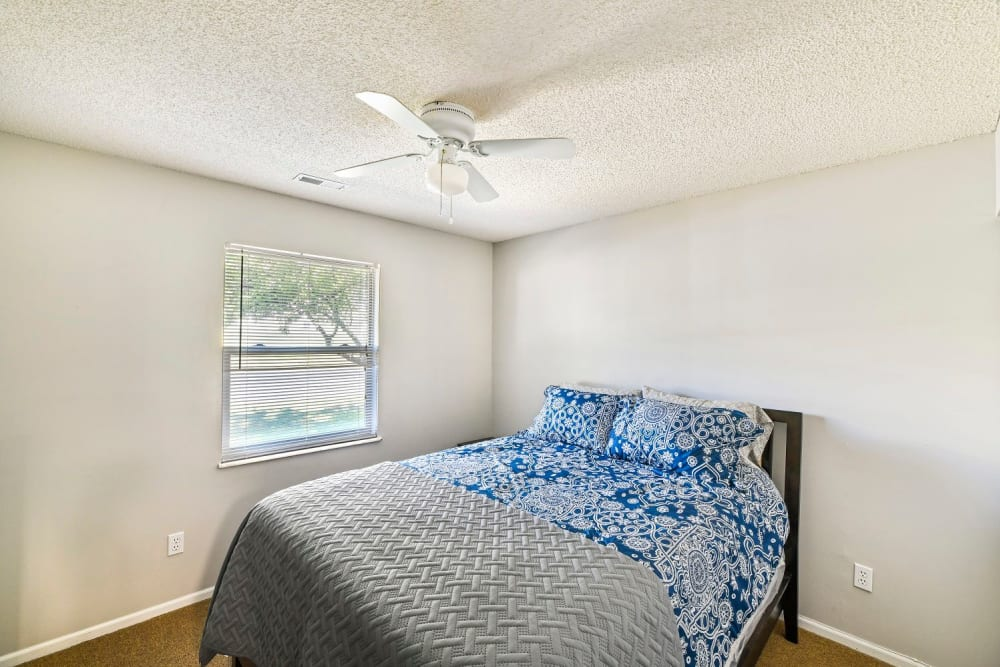 Large master bedroom with a ceiling fan at Creekbend Apartments in Columbus, Ohio