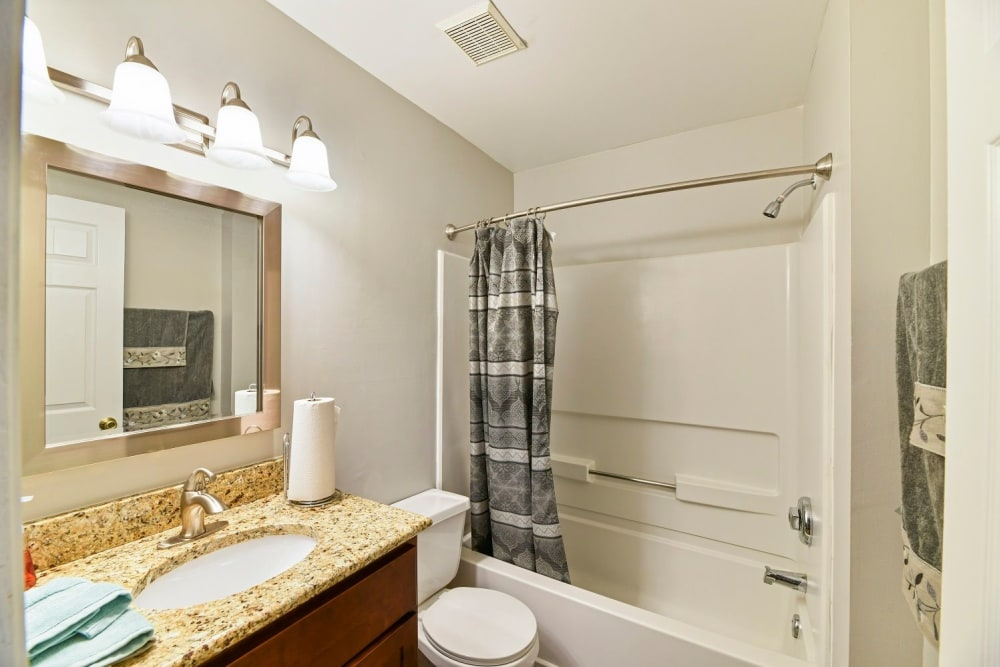 Spacious bathroom with large vanity mirror at Creekbend Apartments in Columbus, Ohio