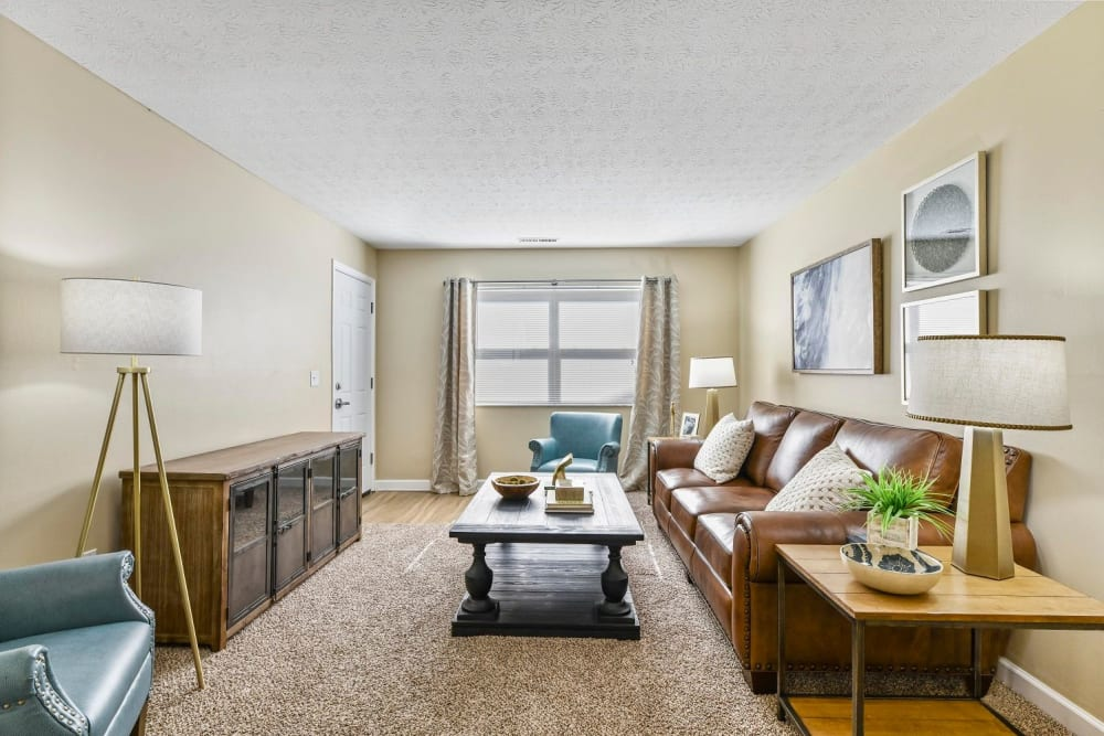 Living room with plush carpeting and a large window for letting in natural light at Hidden Creek Apartment Homes in Columbus, Ohio