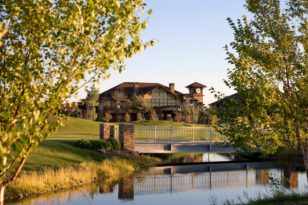 Building exterior and a bridge over the pond at Touchmark at Meadow Lake Village in Meridian, Idaho