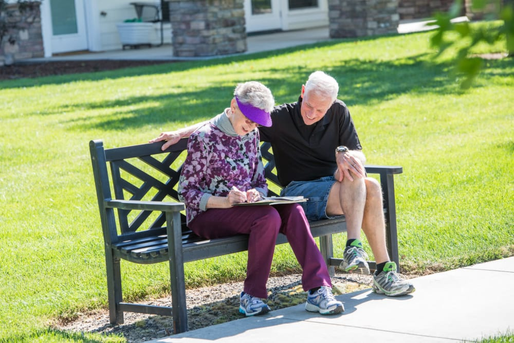 Two residents sitting in the courtyard at Touchmark at Meadow Lake Village in Meridian, Idaho