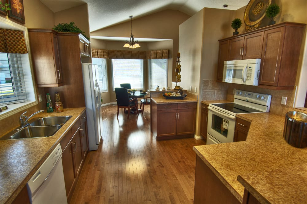 A beautiful kitchen with leading to a dining room at Touchmark at Wedgewood in Edmonton, Alberta
