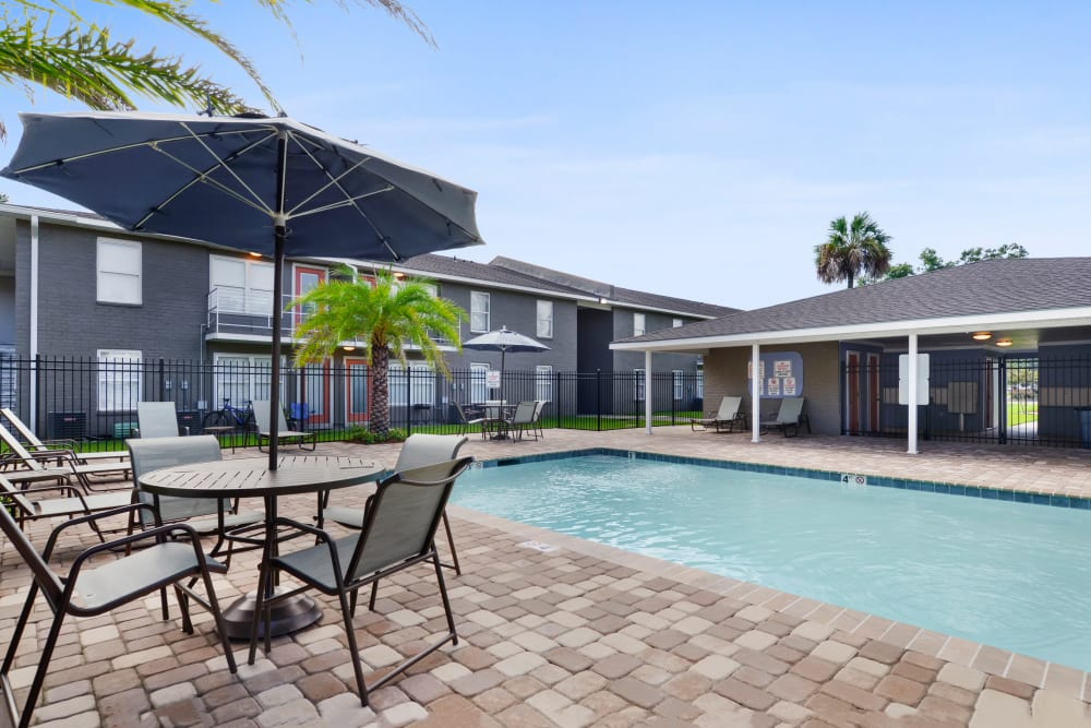 Umbrella and chairs next to swimming pool at Avalon Apartment Homes in Baton Rouge, LA