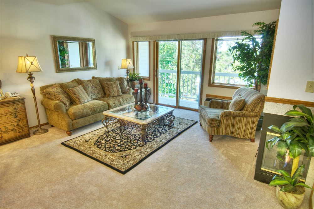 An apartment living room next to a balcony at Touchmark on South Hill in Spokane, Washington