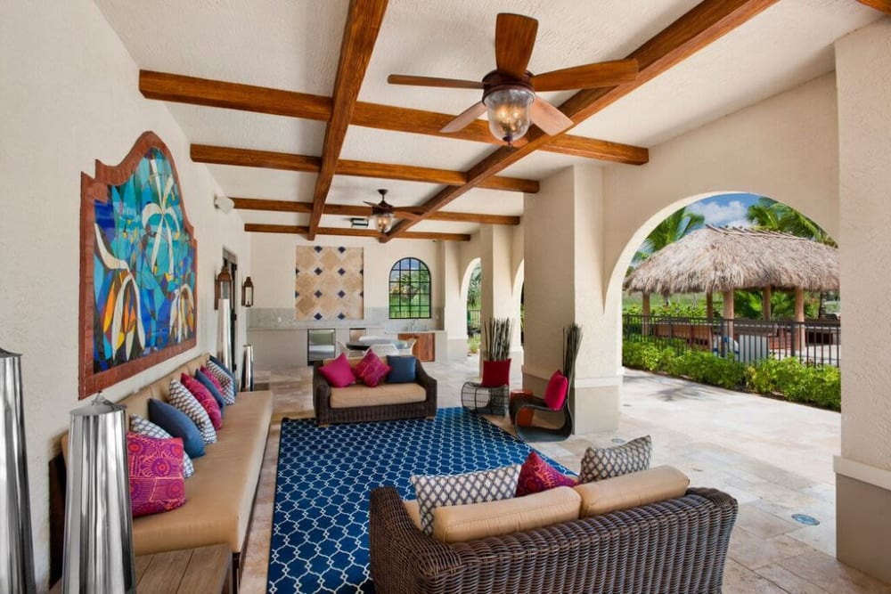 Outdoor covered seating area with lounge furniture and ceiling fans at Doral View Apartments in Miami, Florida