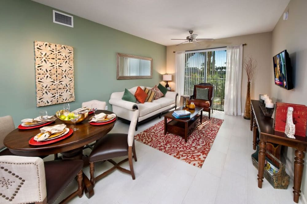 Ceiling fan, an accent wall, and ceramic tile flooring in the living area of a model home at Doral View Apartments in Miami, Florida