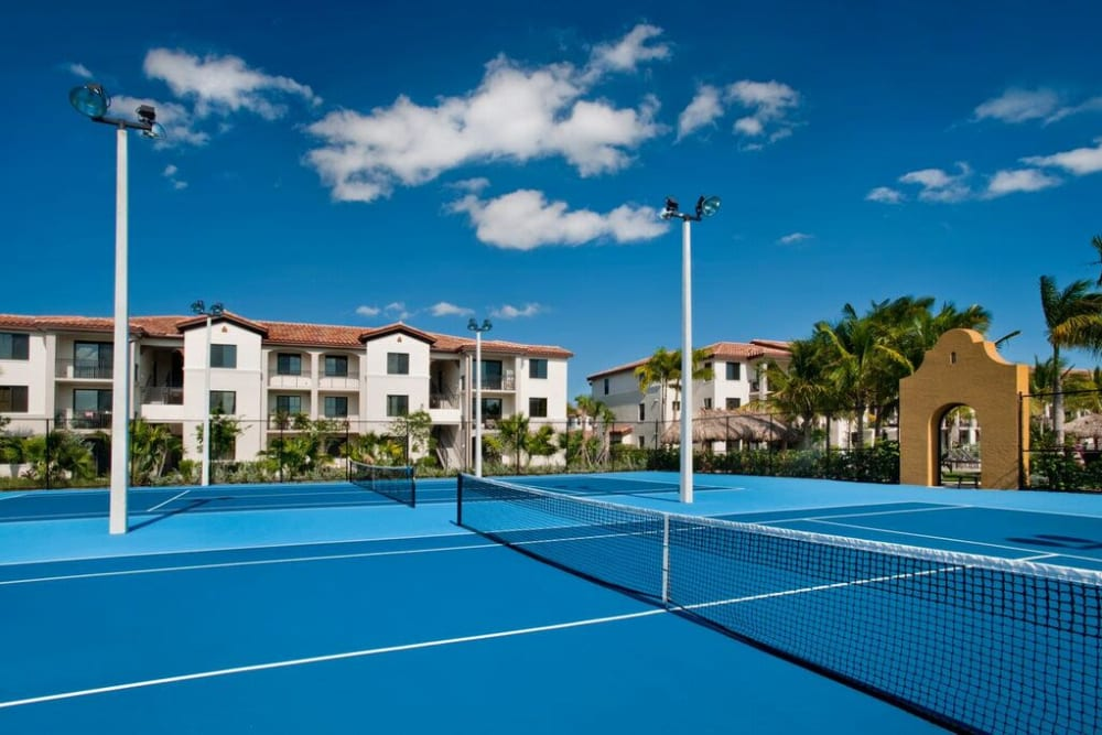 Tennis courts with resident buildings in the background at Doral View Apartments in Miami, Florida