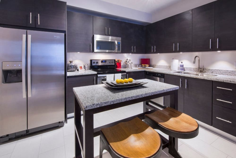 Gourmet kitchen with an island and granite countertops in a model home at Doral Station in Miami, Florida