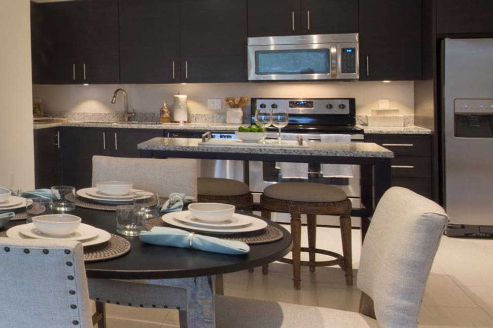 Beautiful gourmet kitchen with dark wood cabinetry and stainless-steel appliances in a model home at Town Fontainebleau Lakes Apartment Residences in Miami, Florida