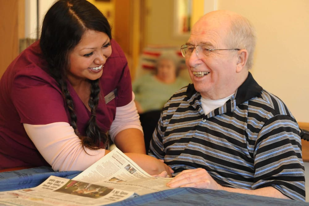 A caretaker reading the paper with her patient at Chandler House in Yakima, Washington