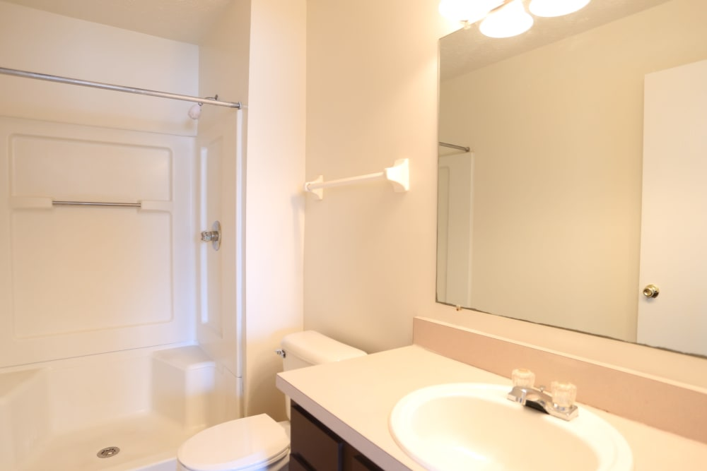 Well-lit bathroom with a large vanity mirror in a model home at Stratford Lakes Apartments in Canal Winchester, Ohio
