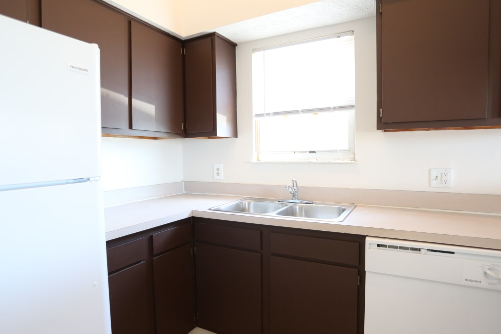 Dark wood cabinetry in a model home's kitchen at Stratford Lakes Apartments in Canal Winchester, Ohio