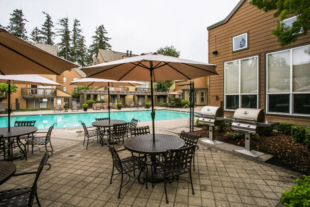 Poolside grills and seating at The Colonnade Luxury Townhome Rentals in Hillsboro, Oregon