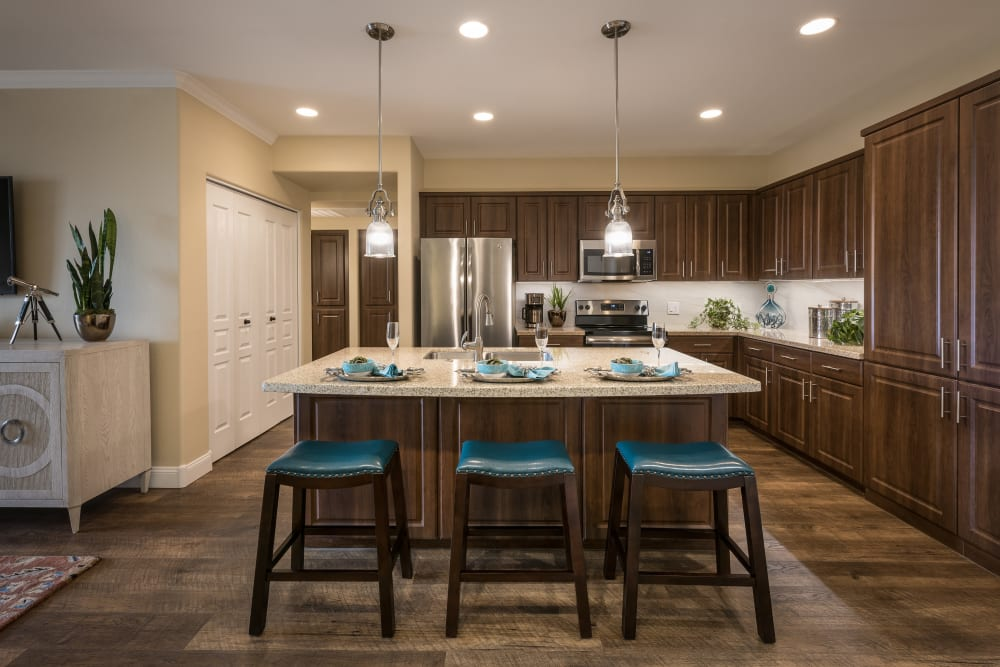 Gourmet kitchen with granite countertops and adjacent workspace in model home at San Valencia in Chandler, Arizona