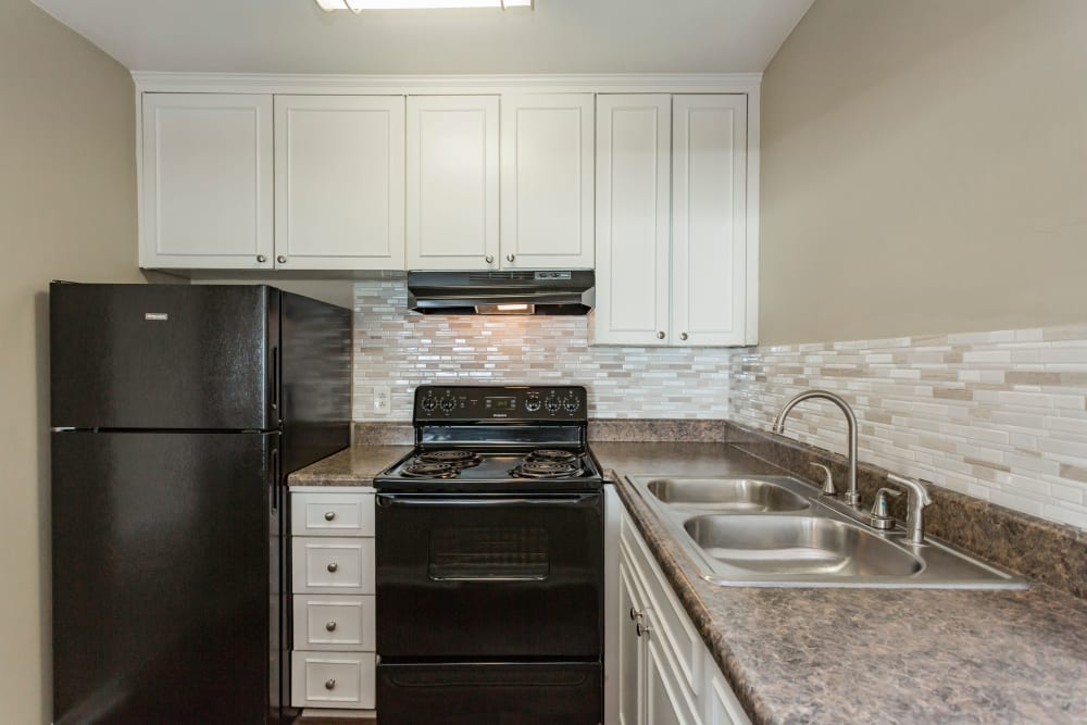 Kitchen with sleek black appliances at Belmont Place in Nashville, Tennessee
