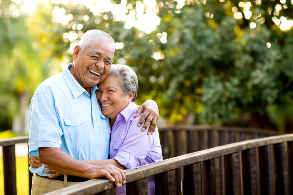 A happy couple hugging outside at Brightwater Senior Living of Highland in Highland, California