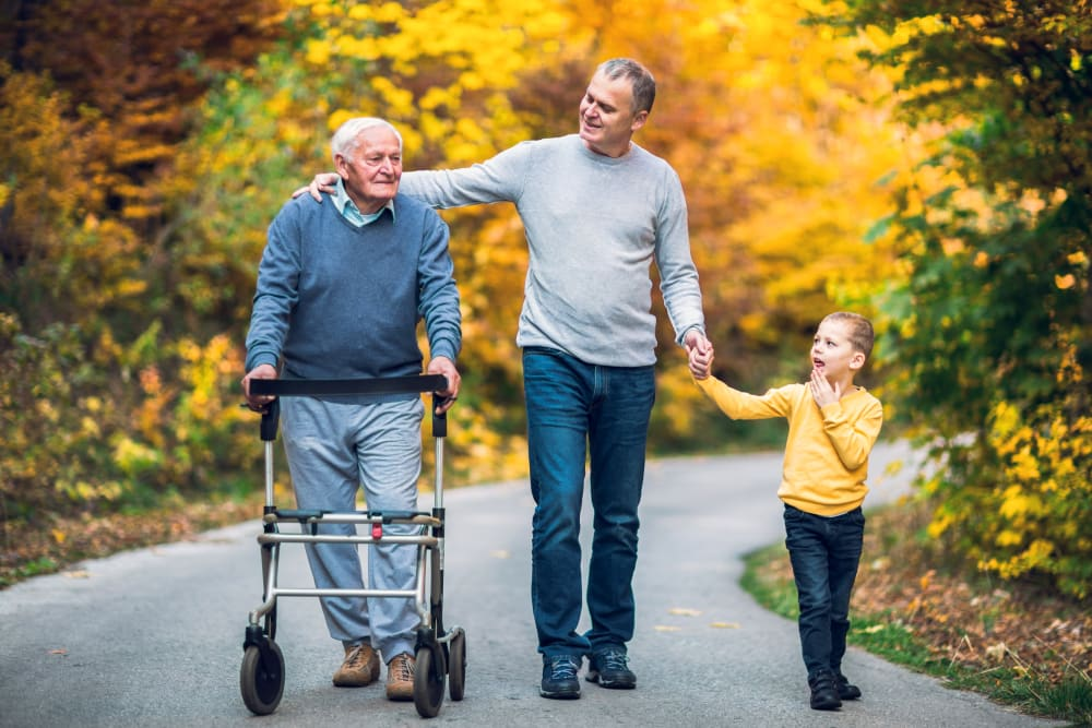 A resident on a walk with his son and grandchild at Brightwater Senior Living of Highland in Highland, California