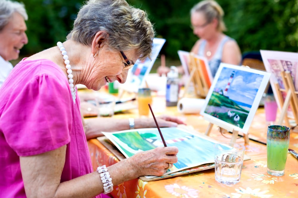 A group of residents painting outdoors at Brightwater Senior Living of Highland in Highland, California