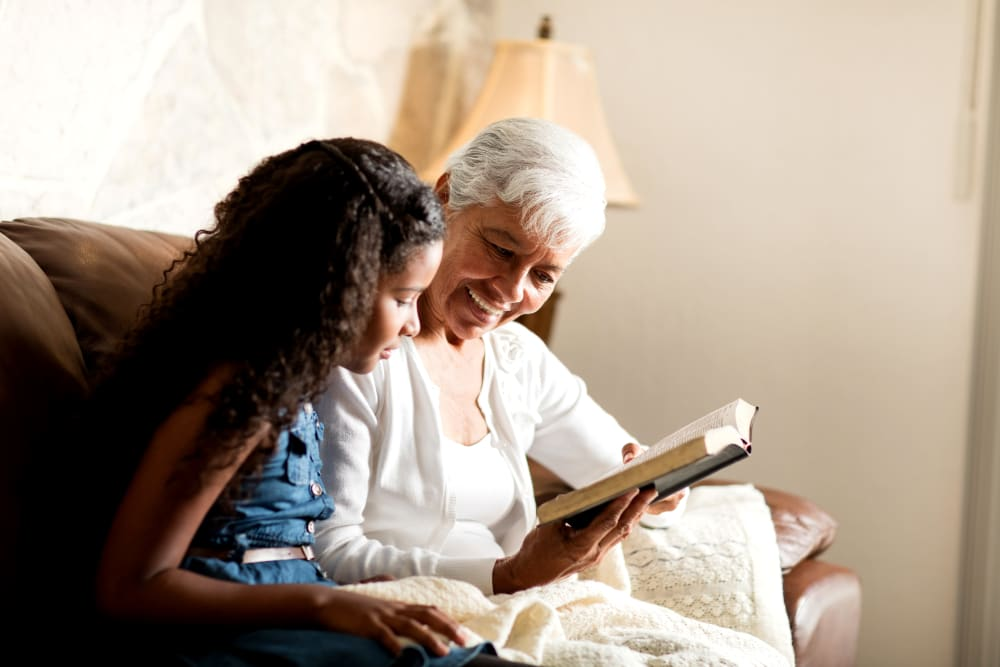 A resident reading to a young child at Brightwater Senior Living of Highland in Highland, California