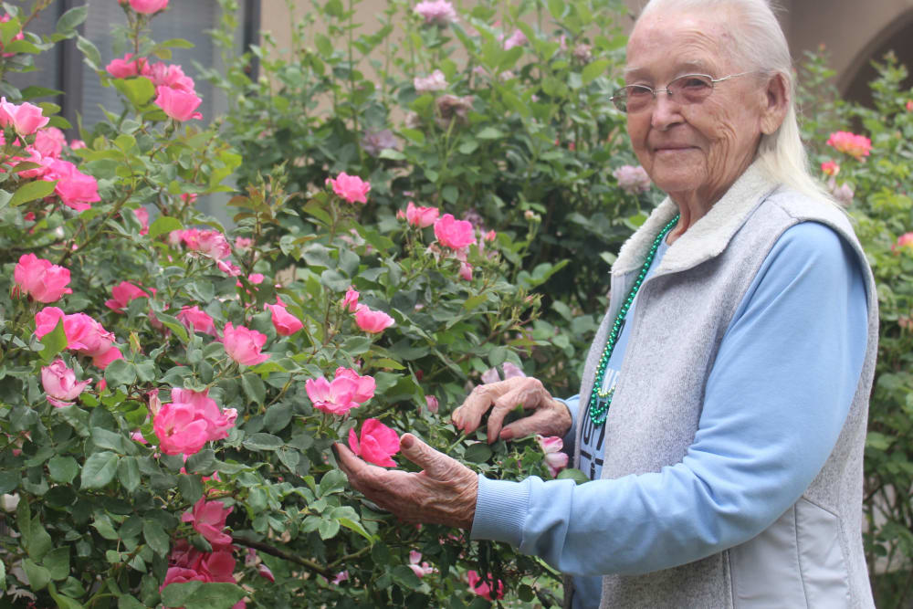 Happy resident with pink flowers at Desert Peaks Assisted Living and Memory Care