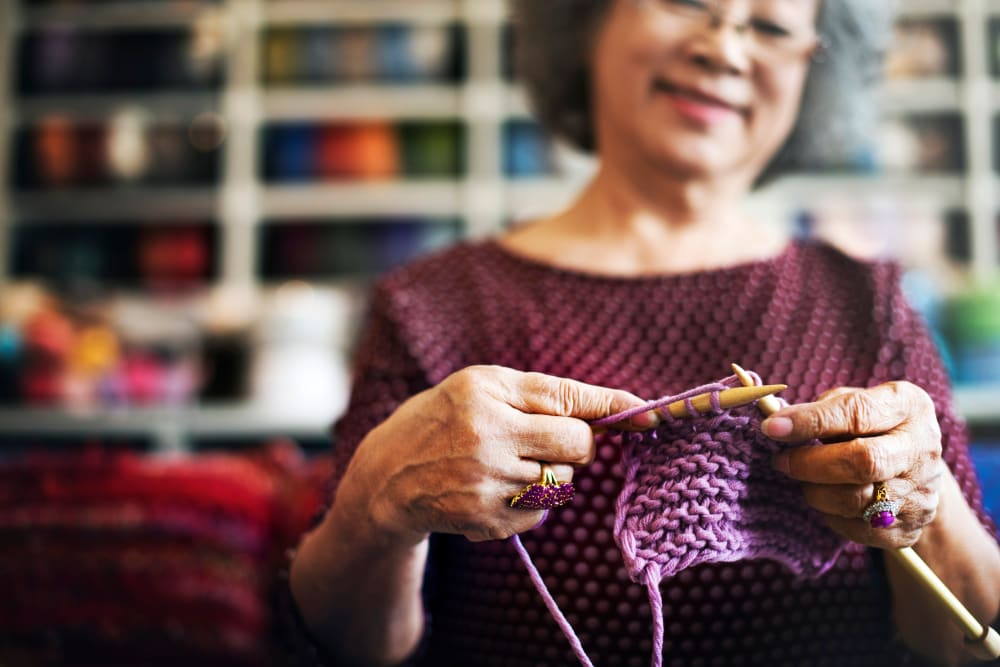 A resident knitting with purple yarn at Carnegie Heights at Henderson in Henderson, Nevada
