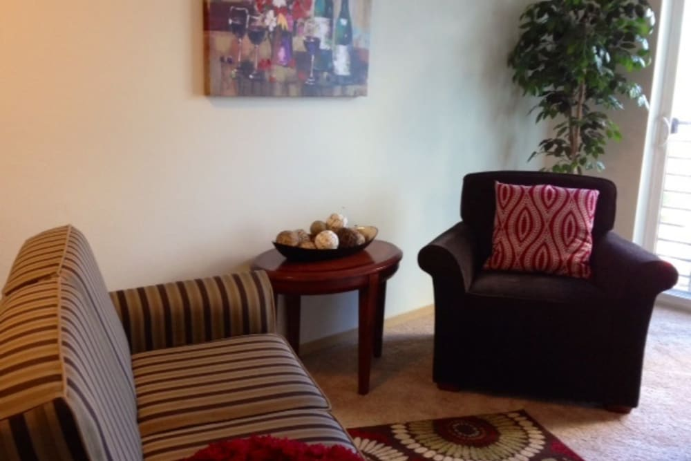 Living room area with a couch and chair at The Heights at Columbia Knoll in Portland, Oregon
