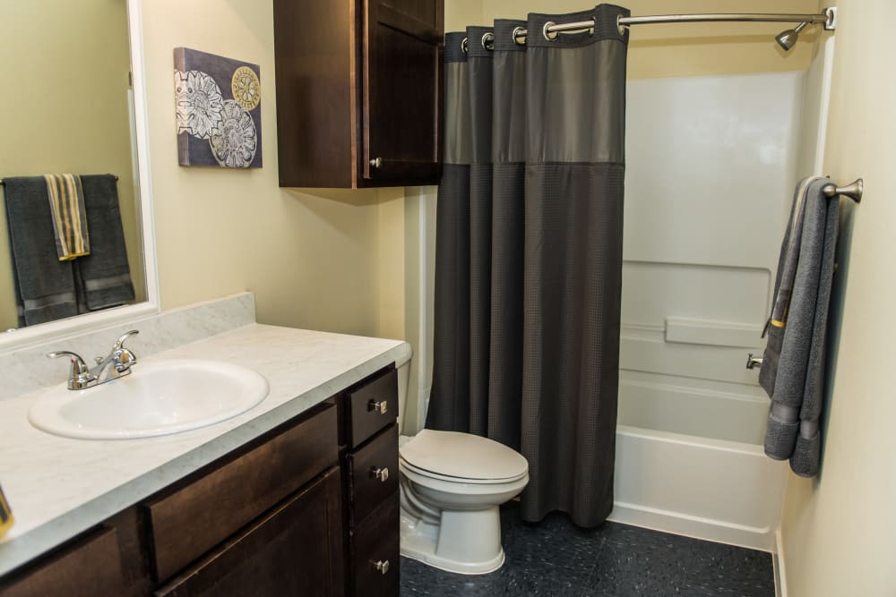 Spacious bathroom with dark wood cabinets at Traditions at Westmoore in Oklahoma City, Oklahoma.
