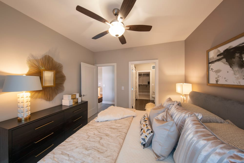 Master bedroom with an en suite bathroom and walk-in closet in a model home at Carter in Scottsdale, Arizona