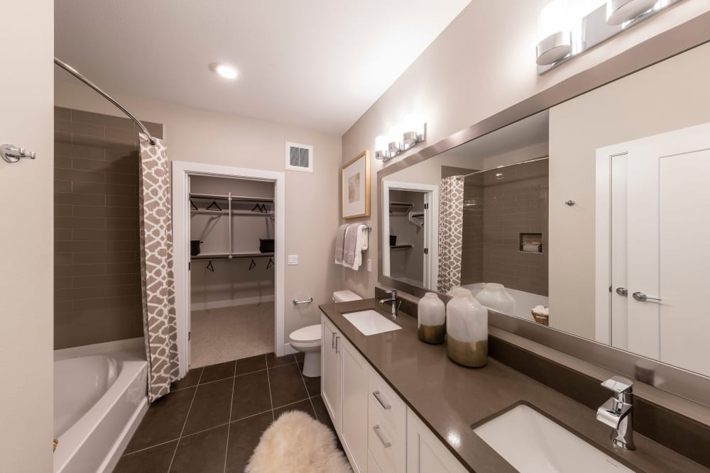 Spacious bathroom with granite countertop and tiling in a model home at Carter in Scottsdale, Arizona