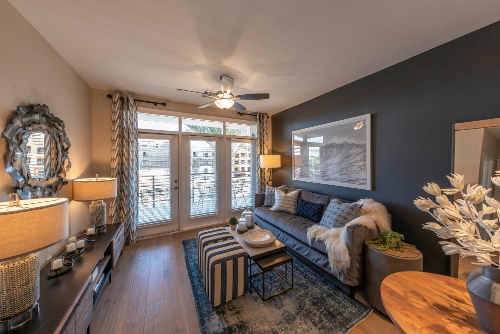 Open-concept floor plans with ceiling fan and hardwood floors in a model home at Carter in Scottsdale, Arizona