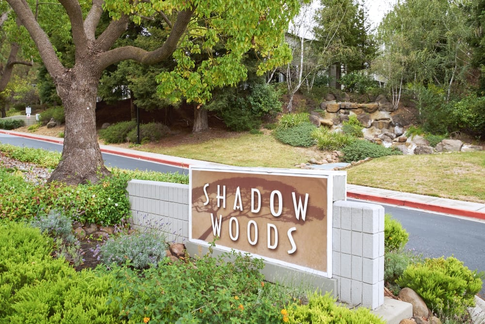 Apartment sign surrounded by a beautifully manicured landscape at Shadow Woods in Oakland, California
