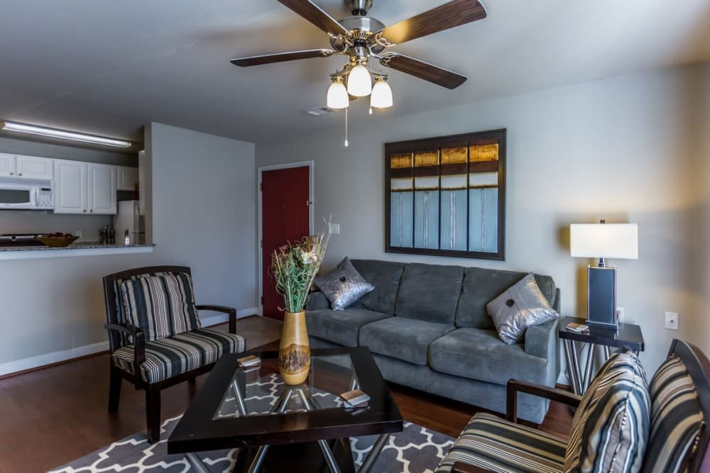 Living room with a ceiling fan at River Pointe in North Little Rock, Arkansas.