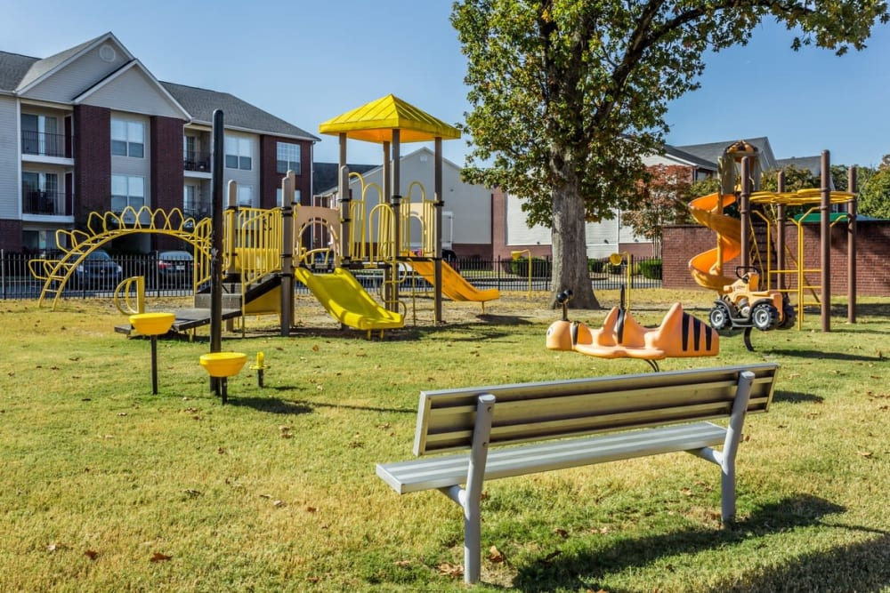 Resident playground with play structures and a bench at River Pointe in North Little Rock, Arkansas.