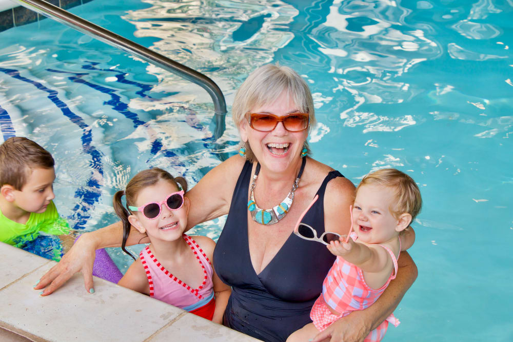 Resident with her grandchildren in the pool at an Integrated Senior Lifestyles community