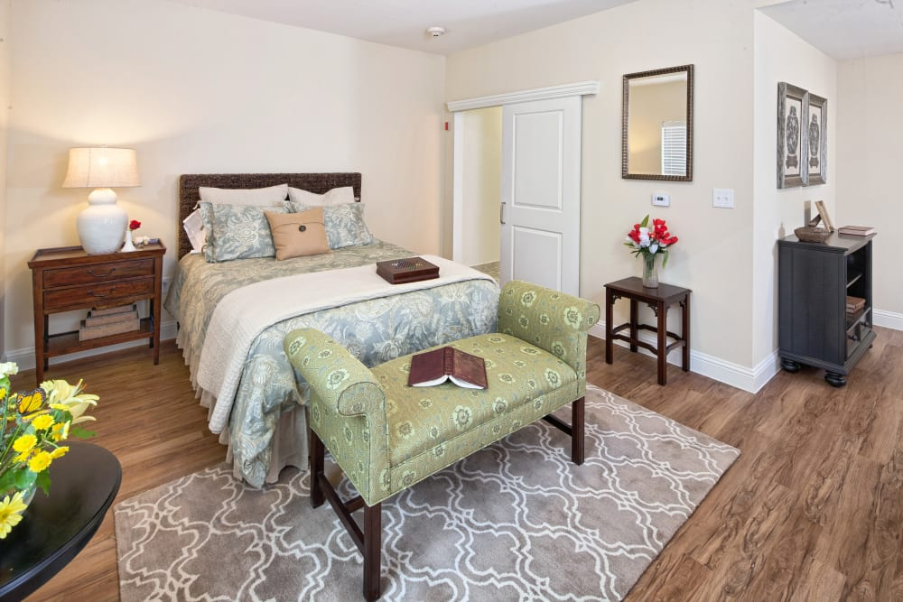 An apartment bedroom with wood-look flooring at The Village of Meyerland in Houston, Texas