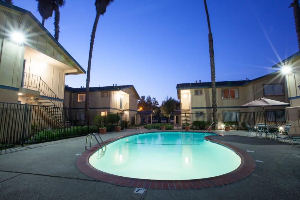 Cedartree Apartments' sparkling, well lit swimming pool at night in Santa Clara, California